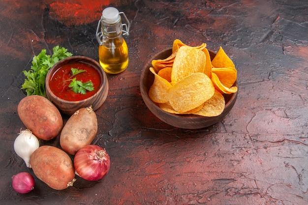 Vista lateral de deliciosas batatas fritas caseiras em uma pequena tigela marrom, alho, ketchup verde, batatas, cebola, óleo, garrafa, ligado, dark table
