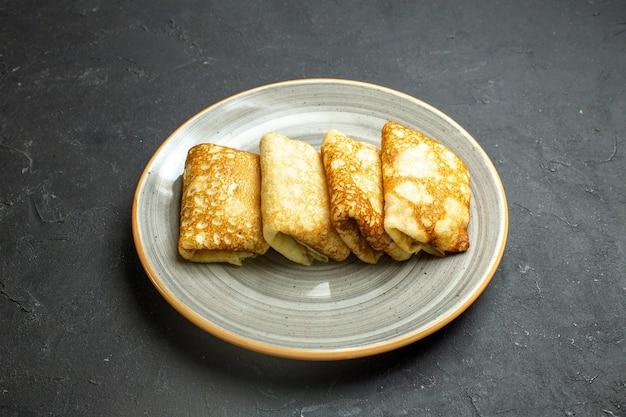 Vista lateral de deliciosas panquecas recheadas de carne em um prato branco sobre fundo preto
