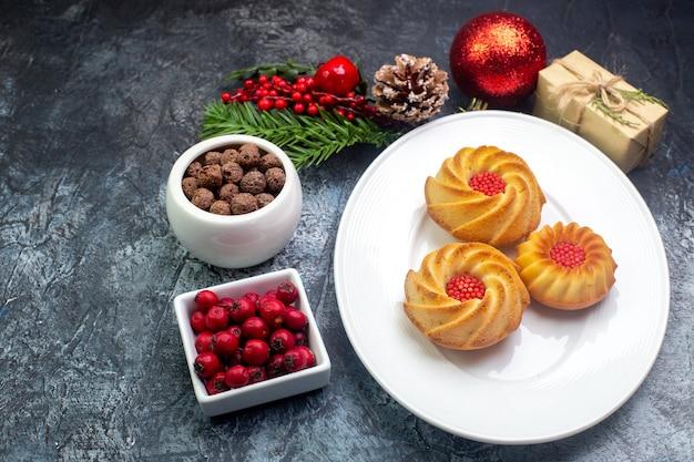 Vista lateral de deliciosos biscoitos em um prato branco e decorações de ano novo presente cornel em uma pequena panela de chocolate na superfície escura