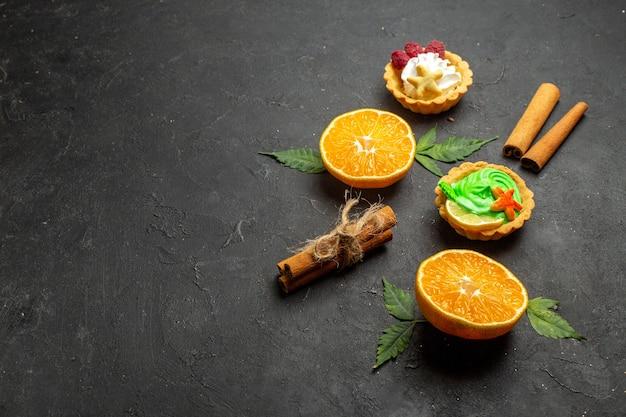 Vista lateral de deliciosos biscoitos, limão, canela e laranjas cortadas pela metade com folhas em fundo escuro