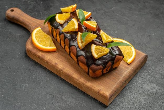 Vista lateral de deliciosos bolos decorados com laranja e chocolate na tábua de cortar na mesa preta