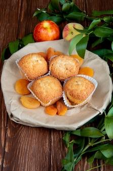 Vista lateral de deliciosos bolos e damascos secos em um prato e nectarinas doces frescas na mesa rústica de madeira