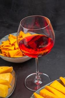 Vista lateral de deliciosos petiscos para vinho em uma taça de vidro em um fundo preto