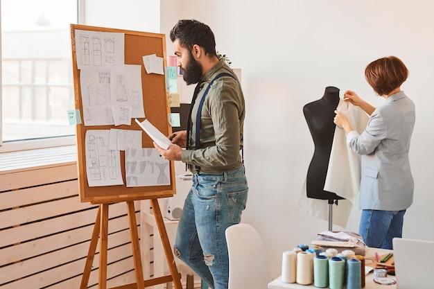 Vista lateral de designers de moda no ateliê com forma de vestido e quadro de ideias