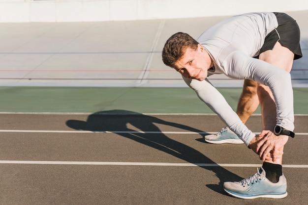 Vista lateral, de, desporto, homem, fazendo, estiramentos