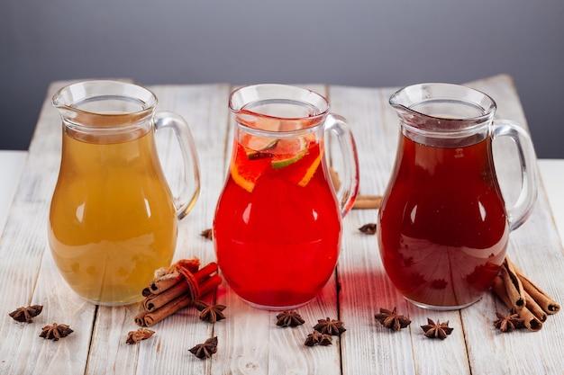 Vista lateral de diferentes limonadas de frutas em jarras de vidro