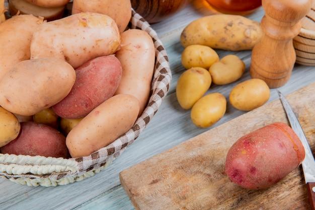 Vista lateral de diferentes tipos de batatas na cesta e corte um com faca na tábua com outros na mesa de madeira