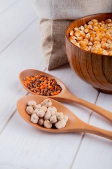 Vista lateral de diferentes tipos de cereais e sementes na tigela e colheres na mesa rústica