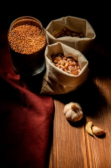 Vista lateral de diferentes tipos de legumes e cereais feijão trigo sarraceno e grão de bico em sacos na mesa escura