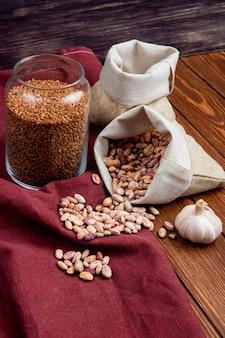 Vista lateral de diferentes tipos de legumes em sacos e trigo cru em uma jarra de vidro na mesa de madeira