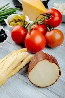 Vista lateral de diferentes tipos de queijo com tomates frescos e azeitonas em conserva na mesa de madeira cinza