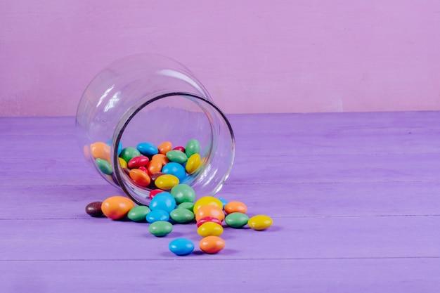 Vista lateral de doces coloridos espalhados de um frasco de vidro no fundo roxo com espaço de cópia