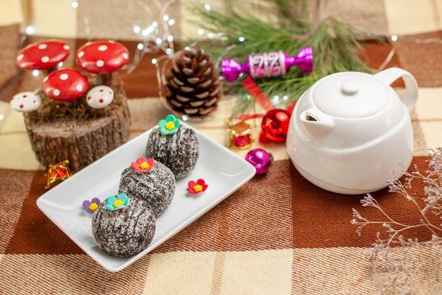 Vista lateral de doces com bule de chocolate branco uma xícara de chá em um pires ao lado do prato de doces de chocolate e galhos de árvores com brinquedos de árvore de natal na toalha de mesa quadriculada