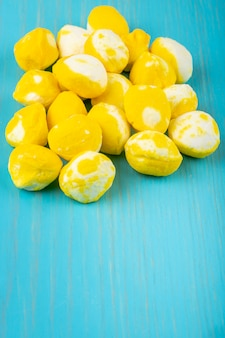 Vista lateral de doces de açúcar doce amarelo sobre fundo azul de madeira, com espaço de cópia