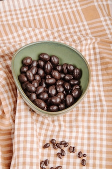 Vista lateral de doces de chocolate porca de vidro em uma tigela na toalha de mesa xadrez