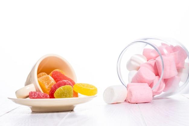 Vista lateral de doces de marmelada colorida e marshmallow espalhados em branco