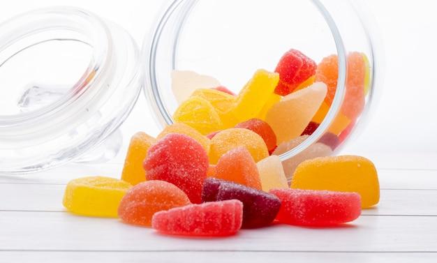 Vista lateral de doces de marmelada coloridos espalhados de um copo na superfície de madeira