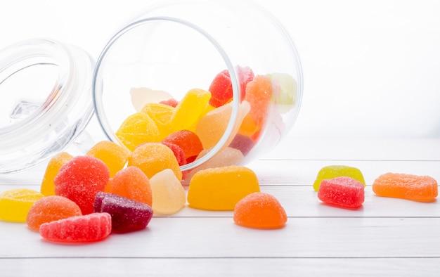 Vista lateral de doces de marmelada coloridos espalhados de um frasco de vidro na superfície de madeira
