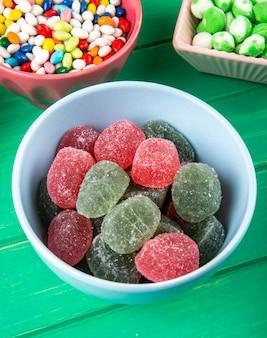 Vista lateral de doces de marmelada doce colorida em uma tigela sobre fundo verde de madeira