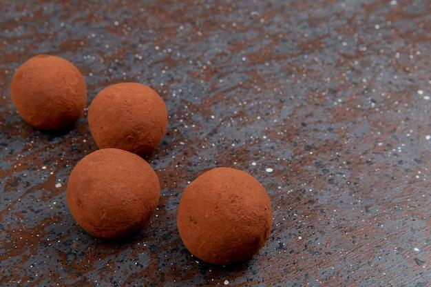 Vista lateral de doces na superfície preta e marrom com espaço de cópia