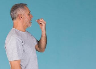 Vista lateral, de, doente, homem, levando, cápsula, contra, experiência azul