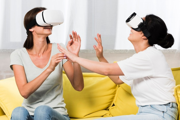 Vista lateral de dois amigos em casa usando fone de ouvido de realidade virtual