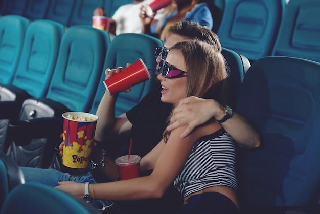 Vista lateral de dois amigos se abraçando e sentados na sala do cinema moderno, assistindo a um filme engraçado. casal positivo de caucasiano, passando o tempo livre no cinema.