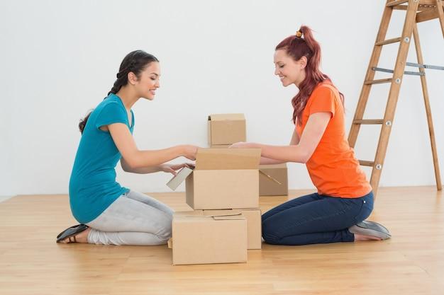 Vista lateral de dois amigos se movendo juntos em uma nova casa