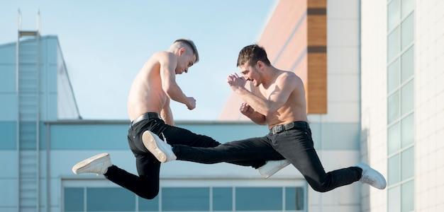 Vista lateral de dois artistas de hip hop sem camisa dançando