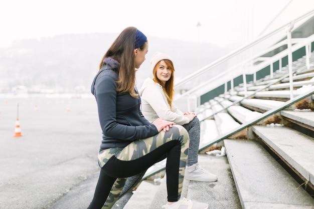 Vista lateral, de, dois, atleta fêmea, esticar, dela, perna, ligado, escadaria, em, inverno