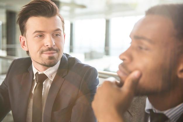 Vista lateral de dois empresários estão olhando para longe.