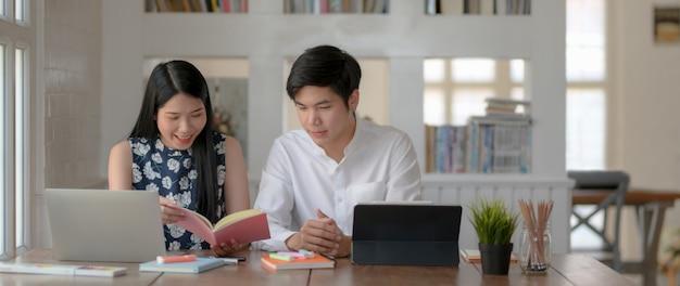Vista lateral de dois estudantes universitários, consultando sua tese na mesa de madeira na biblioteca moderna