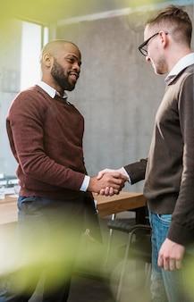 Vista lateral de dois homens apertando a mão em acordo após uma reunião