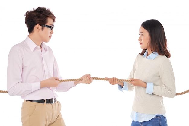 Vista lateral de dois jovens asiáticos puxando a corda que representa a rivalidade