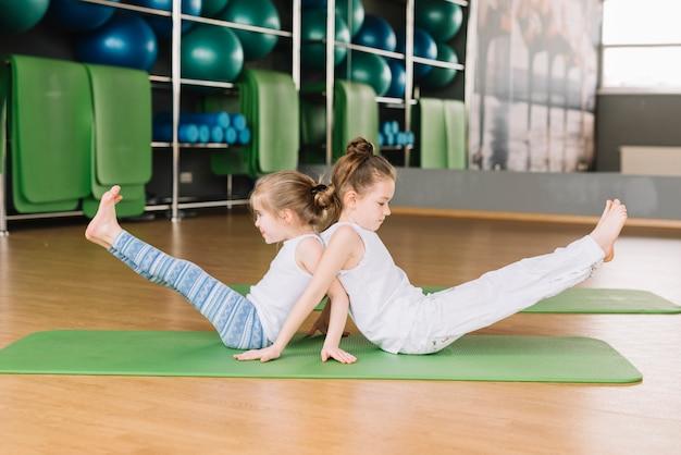 Vista lateral, de, dois, pequeno, menina, criança, fazendo, ioga, exercícios