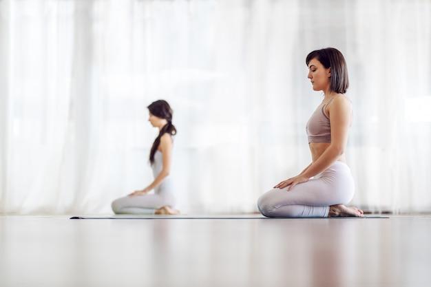 Vista lateral de duas garotas caucasianas atraentes calmas em posição de ioga thunderbolt.