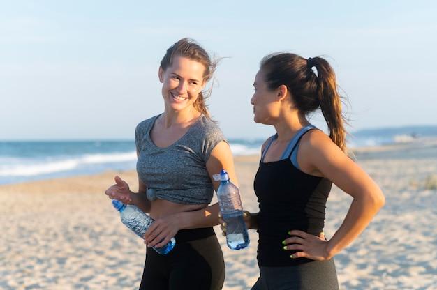 Vista lateral de duas mulheres com garrafas de água durante o treino na praia