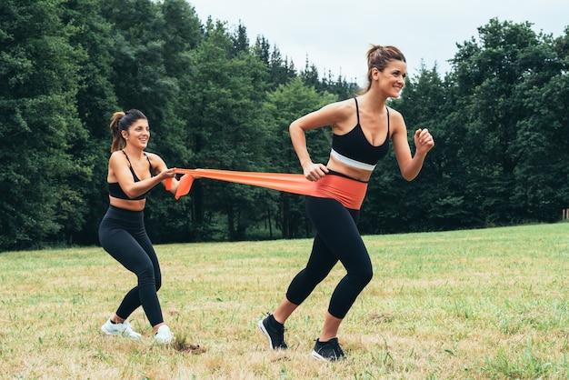 Vista lateral de duas mulheres fazendo exercícios de força com elástico, fazendo muito esforço no meio da floresta