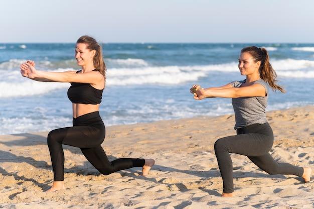 Vista lateral de duas mulheres malhando juntas na praia