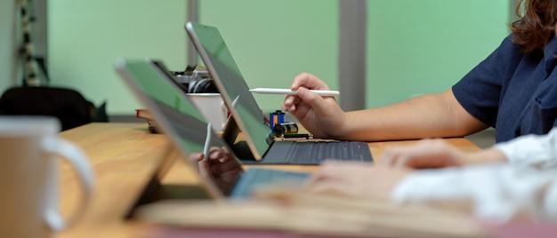 Vista lateral de duas trabalhadoras trabalhando em conjunto com tablets digitais