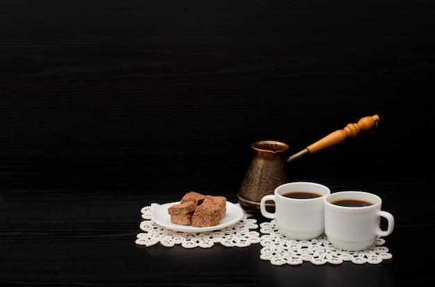 Vista lateral de duas xícaras de café nos guardanapos de renda, sobremesa de chocolate e panelas turcas