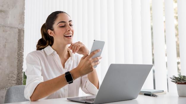 Vista lateral de empresária com smartphone e laptop