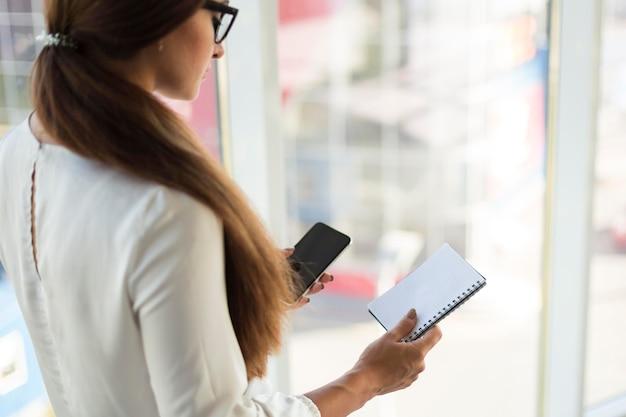 Vista lateral de empresária com smartphone e notebook
