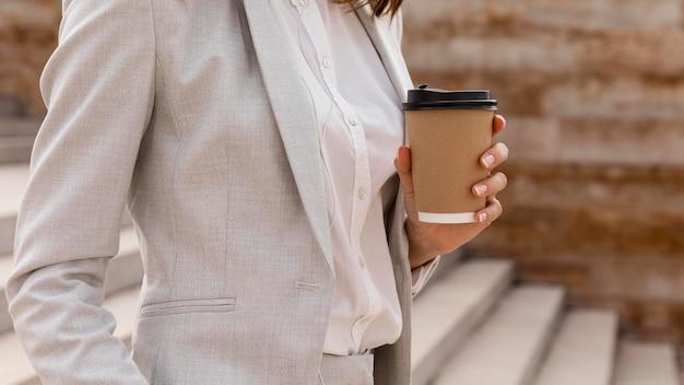 Vista lateral de empresária com xícara de café nas escadas