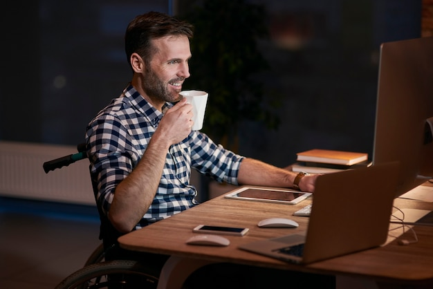 Vista lateral de empresário com deficiência trabalhando até tarde