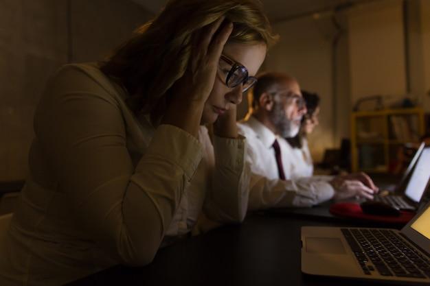 Vista lateral de empresários cansados, trabalhando à noite