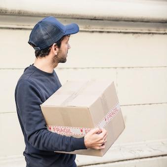 Vista lateral, de, entrega homem, com, pacote
