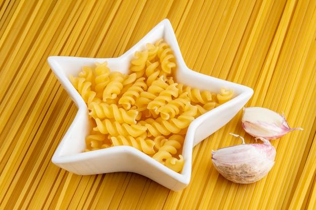 Vista lateral de espaguete cru com alho e macarrão em um pires em forma de estrela