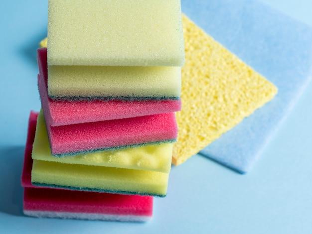 Vista lateral de esponjas de limpeza de diferentes cores e tamanhos dispostas em um fundo azul. produtos de limpeza doméstica