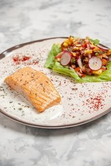 Vista lateral de farinha de peixe e salada deliciosa em um prato na superfície branca manchada